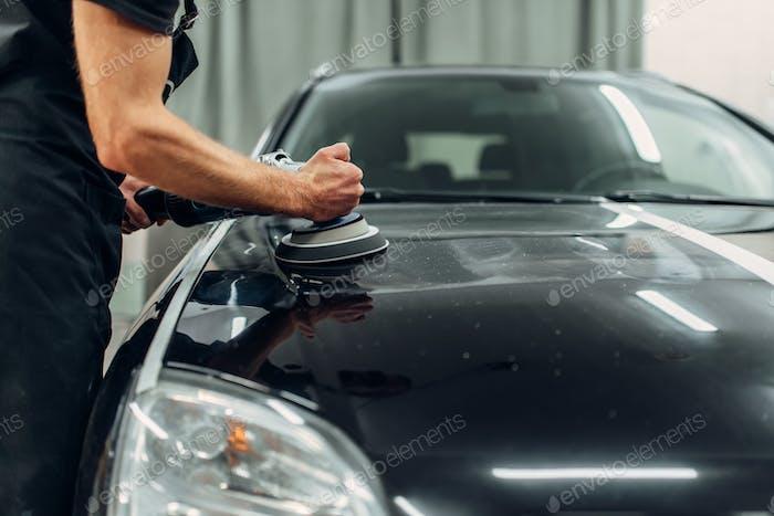 Männliche Person mit Poliermaschine reinigt Auto