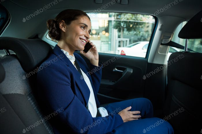 Business executive talking on mobile phone in car