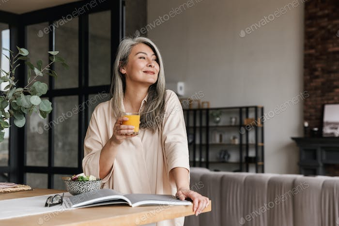 Woman reading book and drinking juice.
