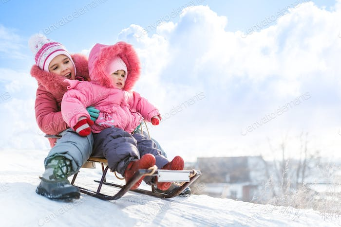 Happy small girls in pink winter clothing sledding downhill on snow
