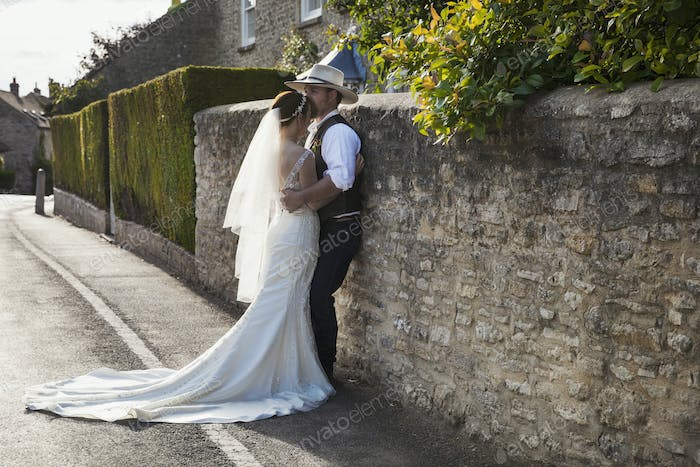 Newlyweds standing outdoors on a pavement, hugging.
