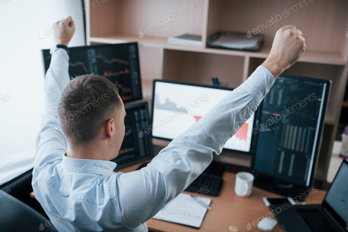 Man working online in the office with multiple computer screens in index charts