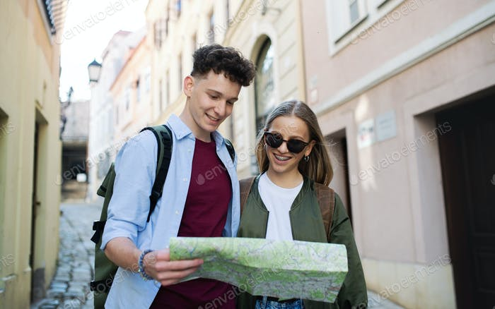 Young couple travelers with map in city on holiday, sightseeing