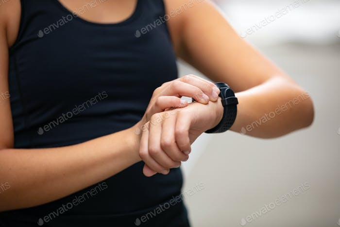 Close-up of woman using fitness smart watch device after running