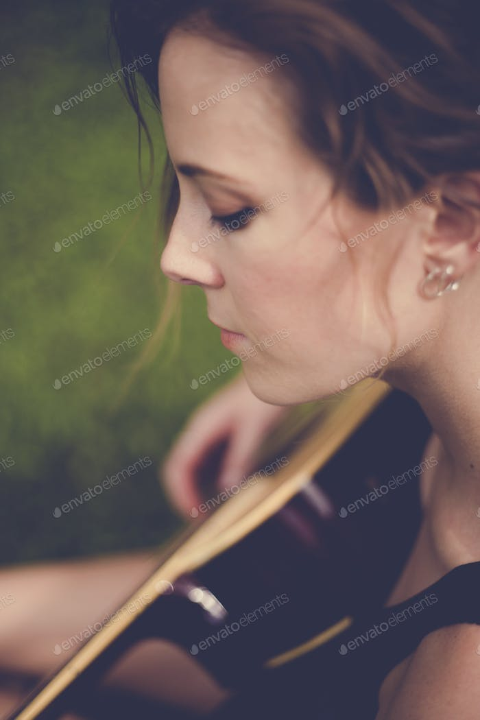 Caucasian woman is sitting and playing guitar classic