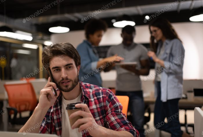 Male worker with drink to go having smartphone conversation