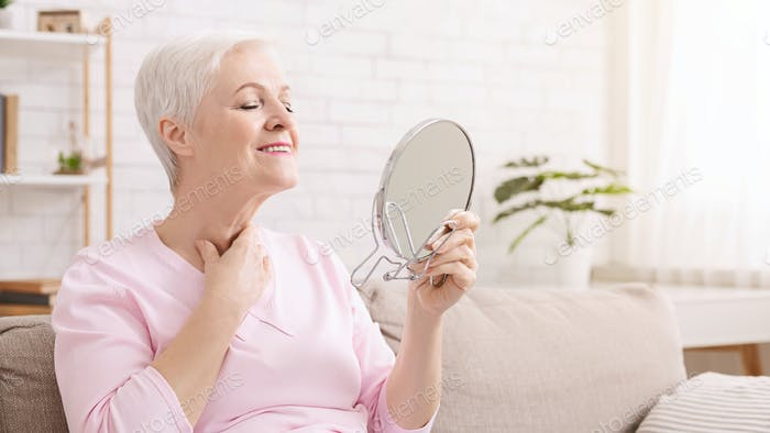 Senior lady looking at mirror, sitting on quarantine at home