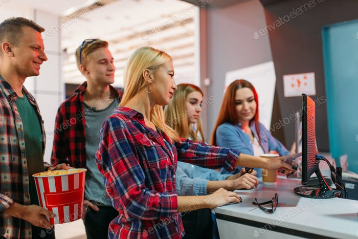 Friends choosing movie in cinema box office