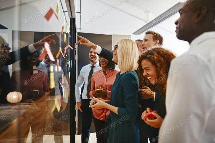 Smiling businesspeople brainstorming together with notes on a glass wall