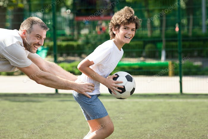 Dad spending time with his son at playground, playing soccer