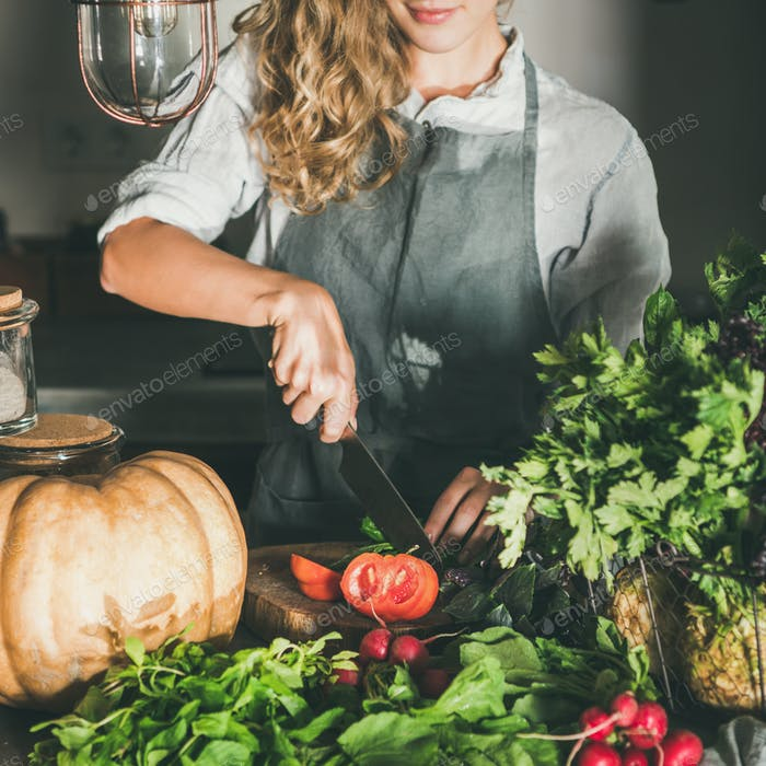 Young woman cutting herbs and vegetables for cooking, square crop