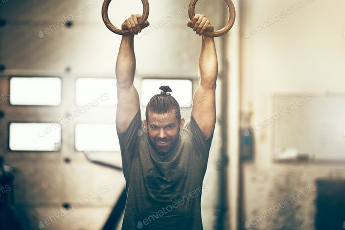 Fit young man exercising on rings at the gym