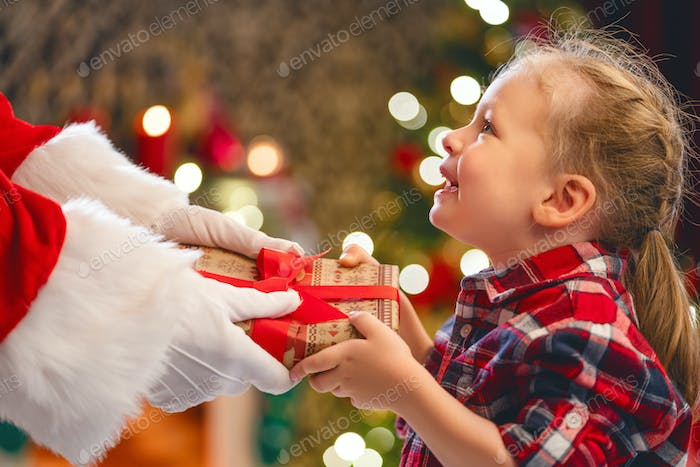 Santa Claus giving gift to child