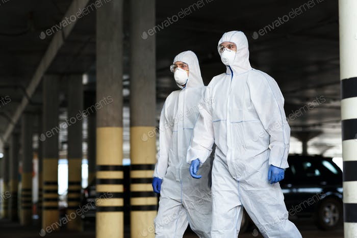 Medical workers in protective mask and suits going in empty city