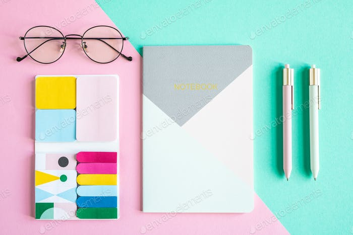 Overview of notebook, two pens, eyeglasses and set of office supplies
