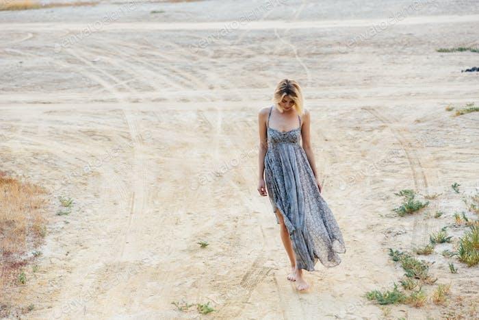 Sad beautiful young woman walking on the road