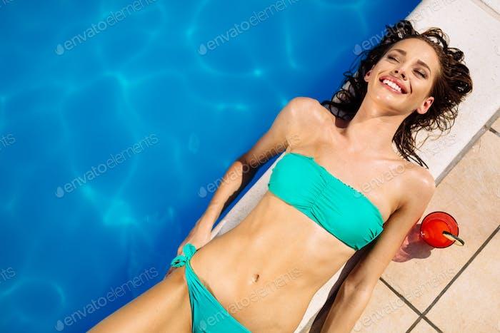 Woman sunbathing at swimming pool