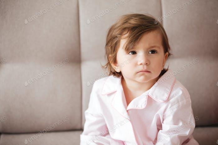 Kind sitzt auf dem Sofa
