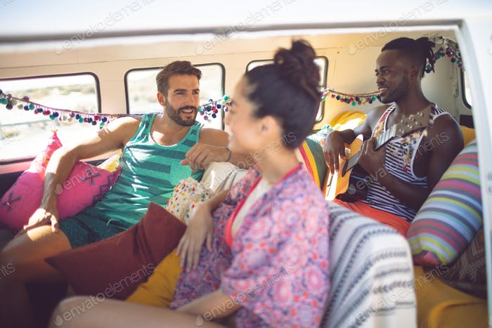 Side view of happy group of diverse friends having fun in a camper van at beach