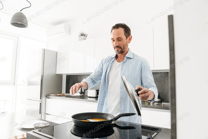 Smiling mature man cooking breakfast