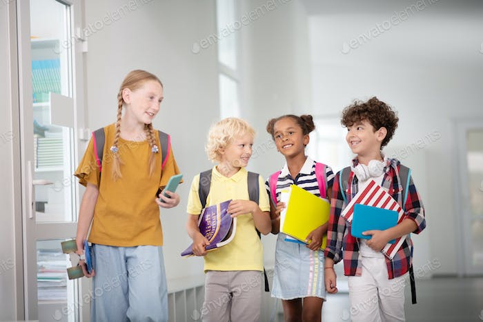 Children with backpacks and books walking to classroom