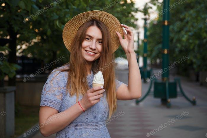 hübsche Mädchen im Sommer Hut ist Essen Eis im freien