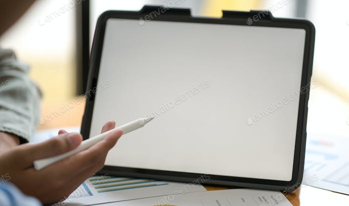 Businessman hand pointing pen at digital tablet to present the project to customers.