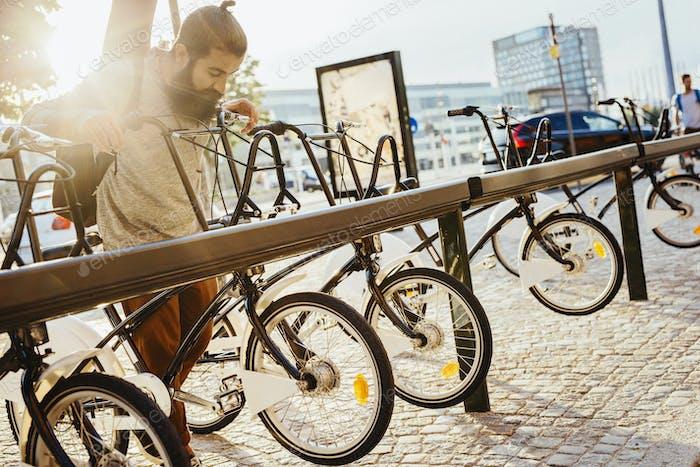 Man taking rental bicycle off rack at station
