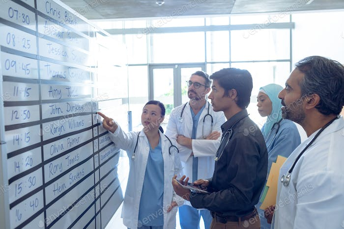 Diverse medical team of doctors discussing their shifts on chart at hospital.