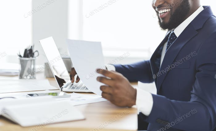 Cropped photo of happy african entrepreneur looking at documents