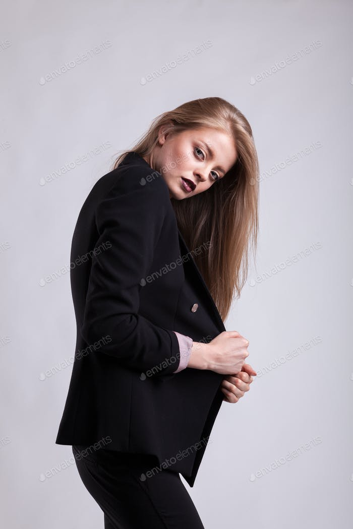 Styled sexy woman in fashion suit on gray background