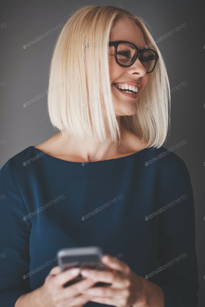 Laughing young businesswoman standing against a gray background reading texts