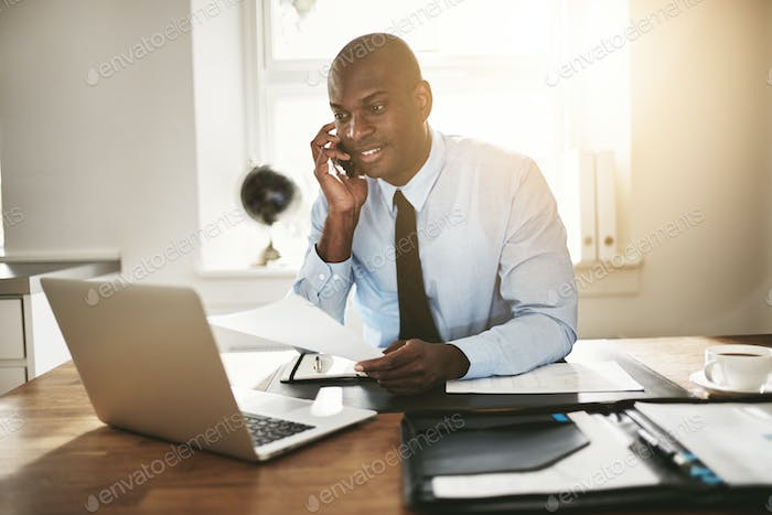 Young businessman reading paperwork over the phone and working online