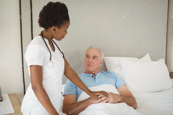 Nurse interacting with senior man on bed