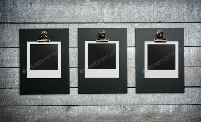 Three blank photos on white wooden background