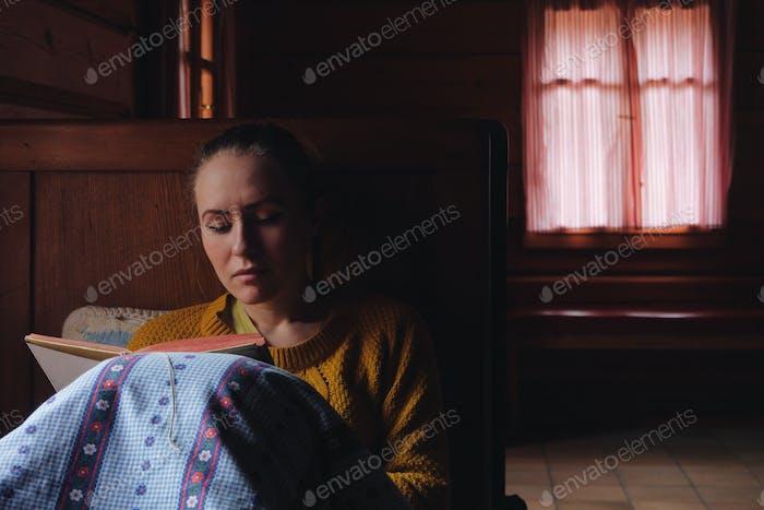 Frau Buch lesen in einem Bett, Holzhaus Interieur