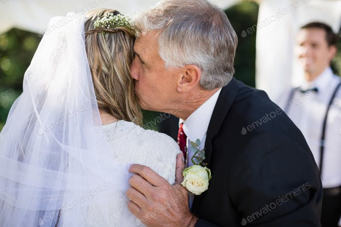 Affectionate father kissing his daughter