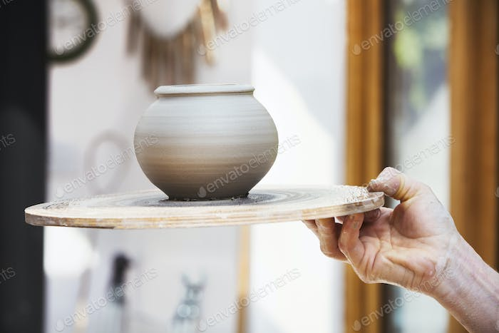 A potter holding a prefired newly thrown pot on a board.