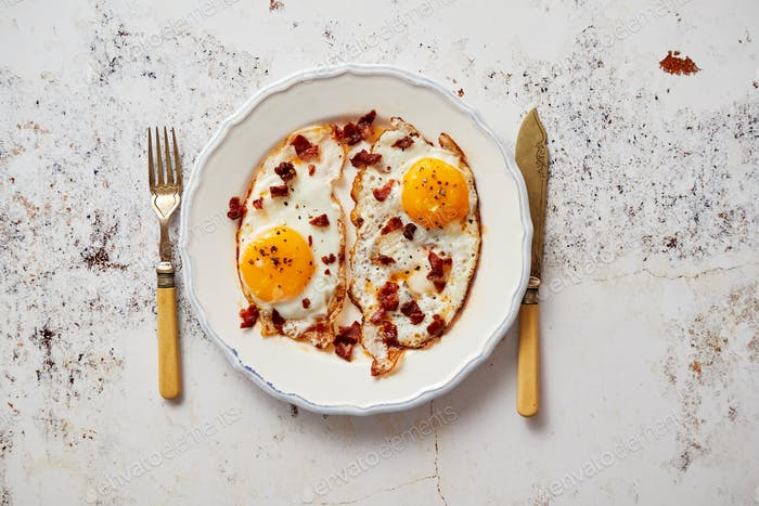 Two fresh fried eggs with crunchy crisp bacon and chive served on rustic plate