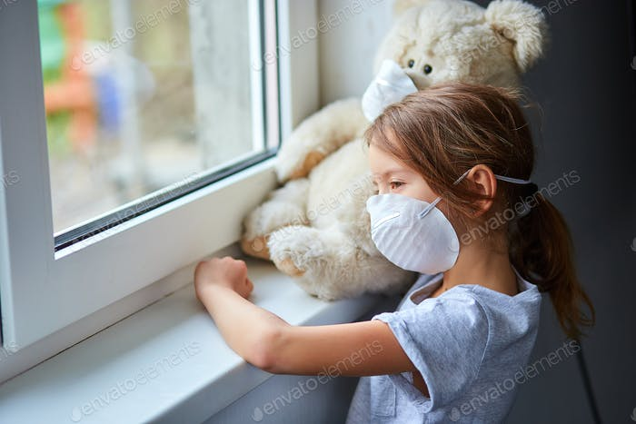 Little girl holding and hugging teddy bear in mask near the window.