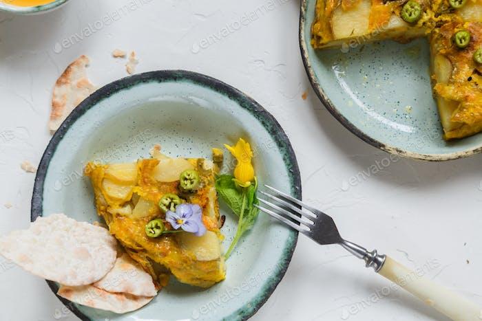 Ein Stück Tortilla oder spanisches Kartoffelomelett auf weißem Hintergrund, Copyspace. Ansicht von oben