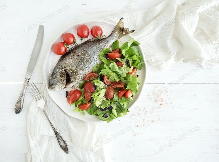 Cooked sea bream fish with fresh vegetable salad on ceramic plate