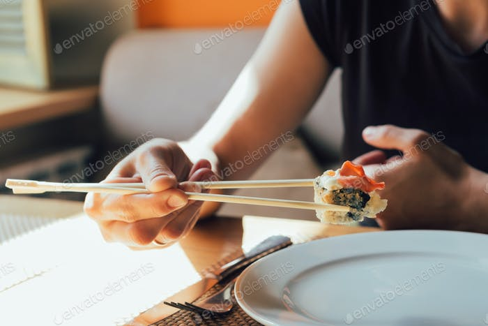 girl eating sushi in restaurant