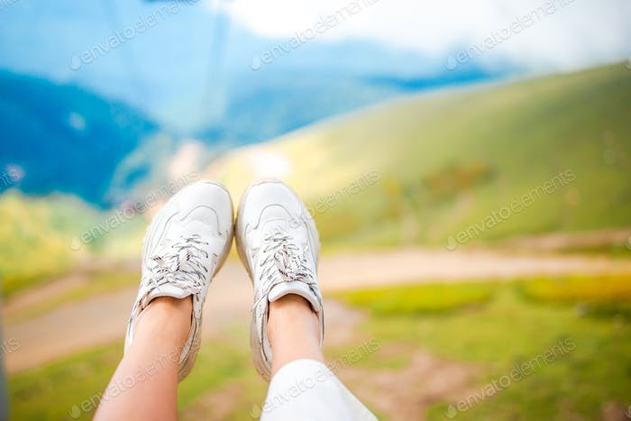Close-up of female legs in sneakers on the grass outdoors in the park
