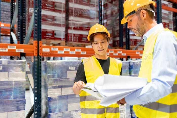 Warehouseman and manager talking about plans of inventory in large warehouse