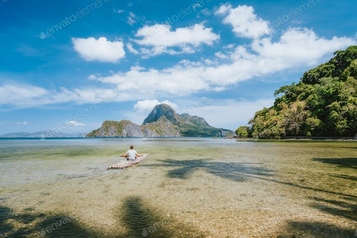Man meditating on bamboo float with impressive view of Cadlao island. Palawan, Philippines. Holiday