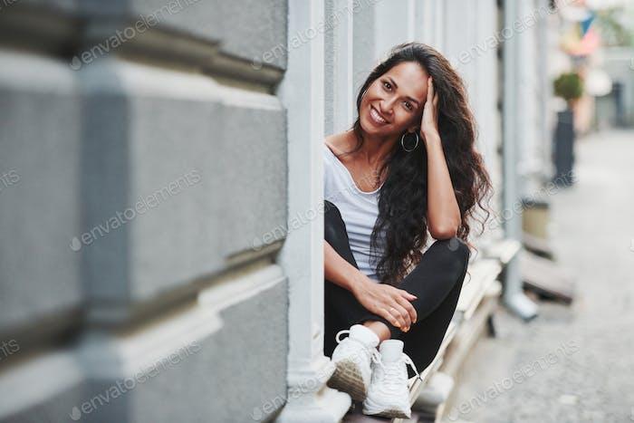 Fröhliche Stimmung. Schöne Frau mit lockigen schwarzen Haaren haben gute Zeit in der Stadt am Tag