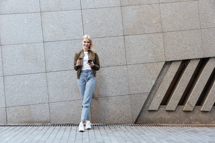 Full-length shot of young woman with cup of coffee and smartphone