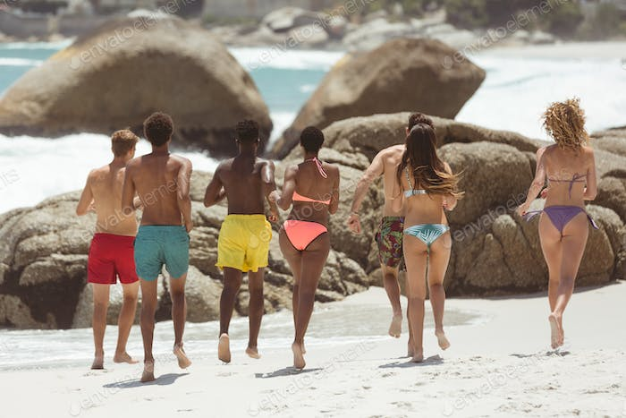 Rear view of multi ethnic group of friends enjoying and runing on sable at beach on sunny day