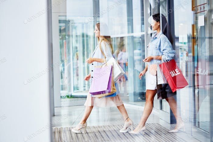 Women Leaving Shopping Center with Paper Bags